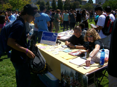 Students sitting at a signup table on Memorial Glade